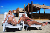Young couple sunbathe on the beach bed on the sea beach — Stock Photo