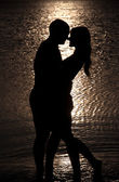 Young couple hug silhouette on a sea beach against sunset backgr — Stock Photo