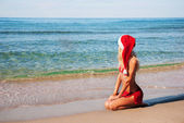 Beautiful woman in santa hat on the sea beach. Christmas or new — Stock Photo