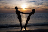 Young couple silhouette on a sea beach holding hands and lookin — Stock Photo
