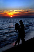 Couple silhouette on beach against sunset — Stock Photo