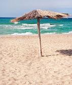 Pure tropical sea beach with the straw beach umbrellas — Stock Photo