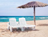 Pure sea beach with the two beach beds and the beach umbrella — Stock Photo