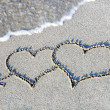 Stock Photo: Two hearts outline on sand against wave