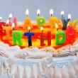 Stock Photo: Appetizing birthday cake with the light rainbow letter candles w