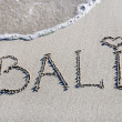 Stock Photo: Word Bali outline on wet sand with wave brilliance