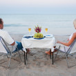 A young couple share a romantic dinner with candles and wine glasses on the sea sand beach — Stock Photo