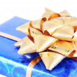 Stock Photo: Blue box with gift golden bow isolated on white