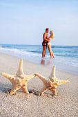 Couple hug on sea sand beach against starfishes — Stock Photo