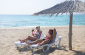 Młoda para opalać się w longue na plaży pod parasol — Zdjęcie stockowe
