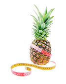 Pineapple and tape measure as reducing weight concept — Stock Photo