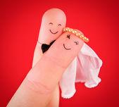 Nowożeńcy uścisk malowane na palce na białym tle na czerwonym tle — Zdjęcie stockowe