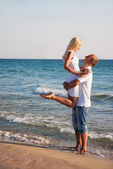 Loving couple hug on sea sand beach — Stock Photo