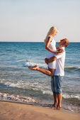 Loving couple hug on sea sand beach — Stock Photo