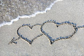Two hearts outline on sand against wave — Stock Photo