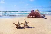 Liebespaar am meer liegenden sandstrand gegen starfishs und schauen einander — Stockfoto
