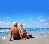 Liebespaar sitzt am meer sandstrand und blick auf den blauen himmel — Stockfoto