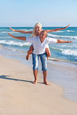 Loving couple flying positive on sea beach — Stock Photo