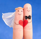 Wedding concept - newlyweds painted at fingers against blue sky — Stock Photo