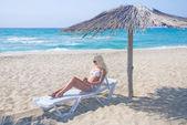 Young cute woman sunbathe in longue on sea beach under sunshade — Stock Photo