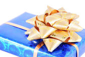 Blue box with gift golden bow isolated on white — Stock Photo