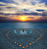 Romantic dinner on sea beach with candles — Stock Photo