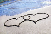 Hjärta kontur på sandstrand med våg — Stockfoto