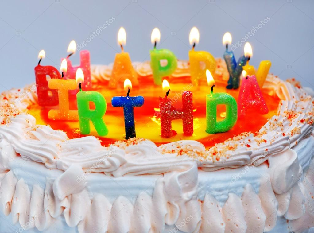 Bolo de aniversário apetitoso com a carta de arco-íris de luz velas ...
