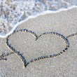 Heart outline on beach sand against wave — Stock Photo