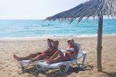 Young couple sunbathe in longue on sea beach under sunshade — Stock Photo