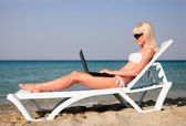Cute blonde woman with white laptop on the summer beach — Stock Photo