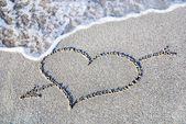 Heart outline on beach sand against wave — Stock Photo