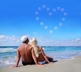 Láska koncepce - pár na mořské pláži pohled na oblačno srdce — Stock fotografie