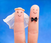 Just married concept - newlyweds painted at fingers against blu — Stock Photo