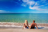 Young couple sitting on the sea sand beach and look at sky — Stock Photo