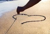 Heart outline on wet brilliance sand — Stock Photo