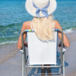 Blonde woman in white straw hat sitting on beach chair and look — Stock Photo