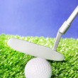Golf ball and club on green field grass against blue sky — Stock Photo #25796465