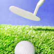 Golf ball and club on green field grass against blue sky — Stock Photo