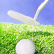 Golf ball and club on green field grass against blue sky — Stock Photo #25796483