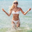 Stock Photo: Cute blonde womin white bikini in water splashes at sea