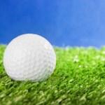 Golf ball on green field grass against blue sky — Stock Photo