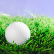 Golf ball on green field grass against blue sky — Stock Photo