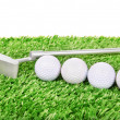 Golf balls and club on green grass — Stock Photo