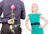 Loving couple - man with rose surprise for his woman — Stock Photo