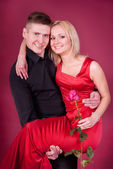 Young couple portrait. Woman in red dress with rose, and man hold her arms — Stock Photo