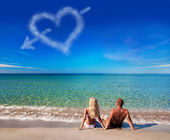 Love concept - young couple on sea beach look at cloud heart — Stock Photo