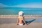 Cute blonde woman in white bikini on sea sand beach — Stock Photo