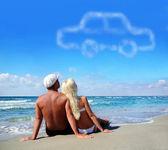 Jovem casal na areia do mar praia sonhando com o próprio carro — Foto Stock