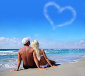 Love concept - couple on sea beach look at cloudy heart — Stock Photo